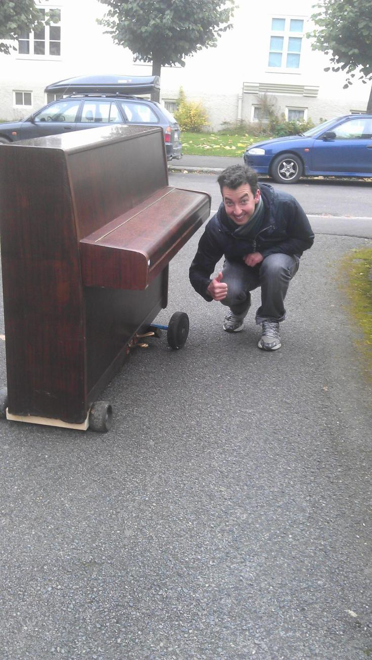 A posing in front of our piano on the street